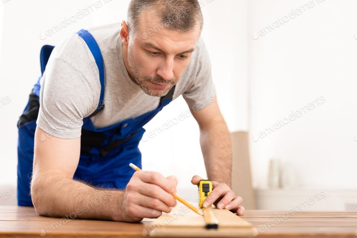 Craftsman Working With Wooden Board Making Furniture In His Studio