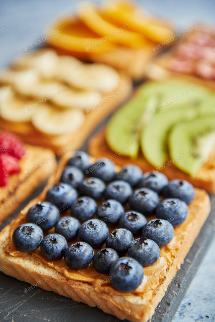 Six toasts with peanut butter, fresh fruits on a grey slate