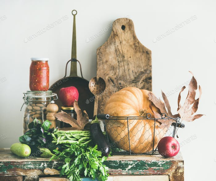 Autumn seasonal food ingredients and kitchen utensils over wooden cupboard