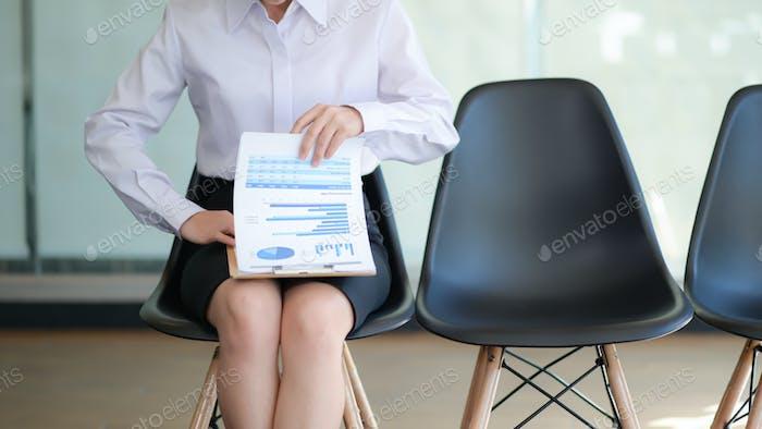 Chica sentada en la silla preparando currículum para la entrevista de trabajo.