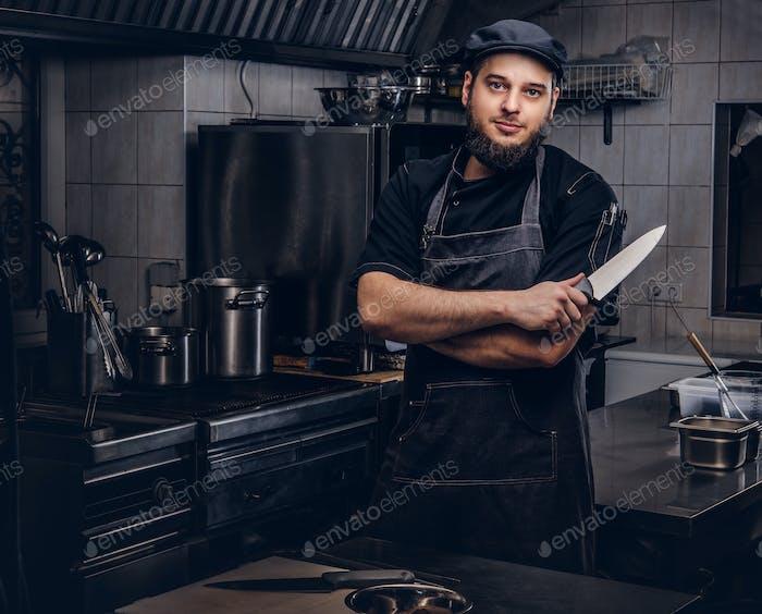 Бородатый повар в черной форме и шляпе держит нож, стоя со скрещенными руками на кухне.