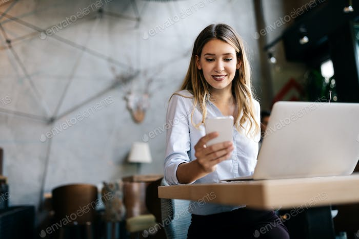 Happy young beautiful woman working, surfing, studying on laptop