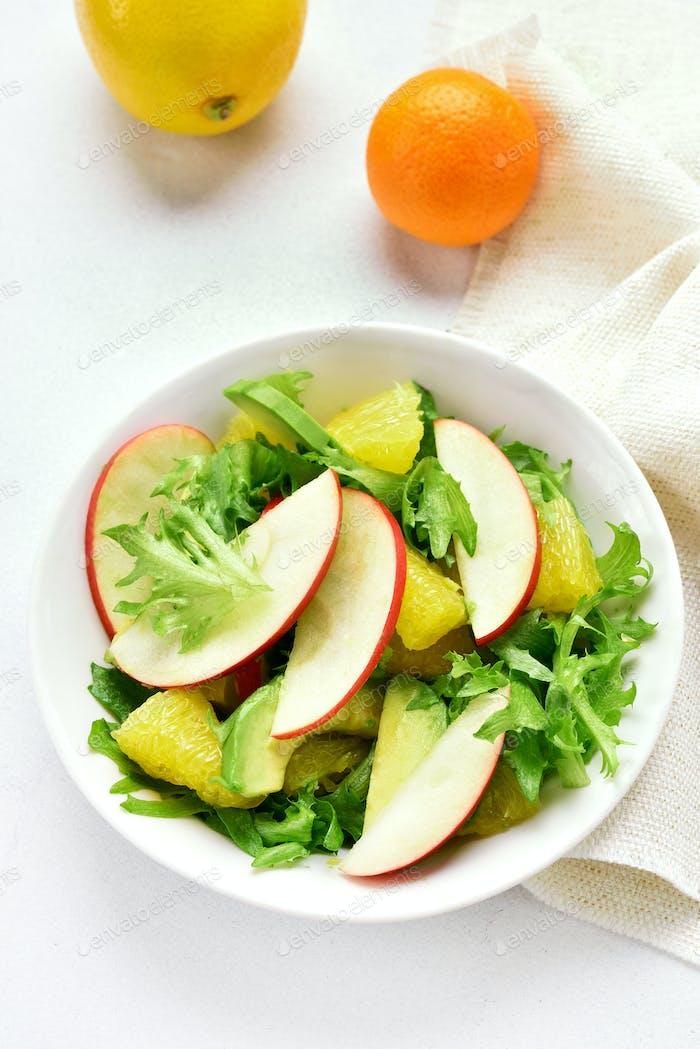 Fruit vegetable salad with red apples, avocado, orange slices