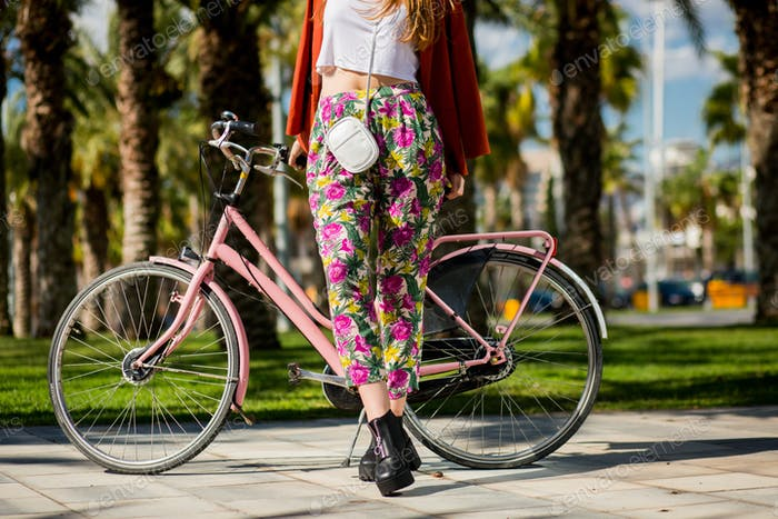 Fashion portrait of pretty blonde woman posing with cruiser in Barcelona
