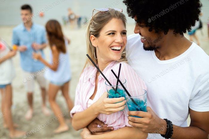Schönes Paar hat Spaß am Strand, trinken und lächelnd