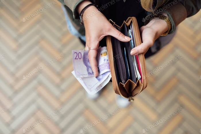 Woman holding open wallet with banknotes and receipts