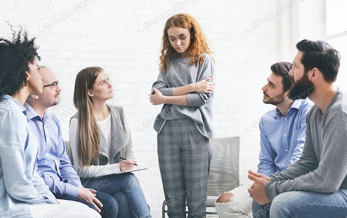 Addicted woman talking talking during rehab group meeting