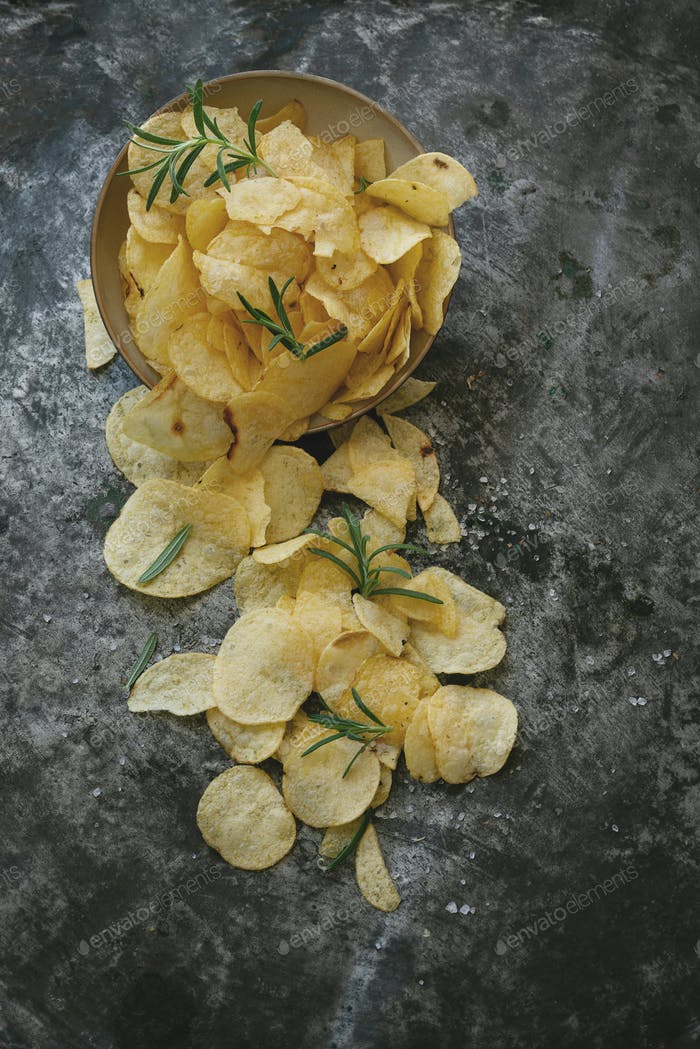 Crispy potato chips in ceramic bowl with salt and seasonings
