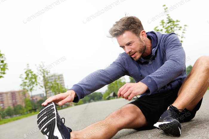 Sitting male runner doing stretch