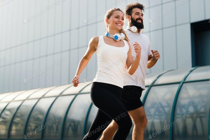 Junges Fitnesspaar läuft im Stadtgebiet