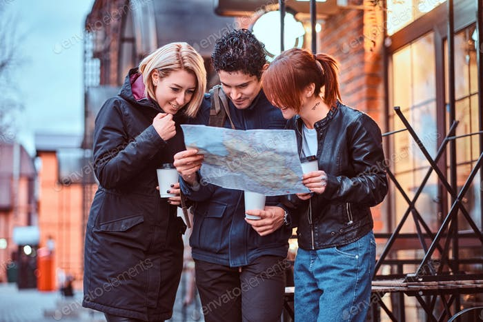 Group of tourists searching place on the map