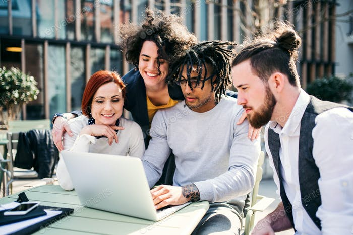 Group of young businesspeople using laptop in courtyard, start-up concept