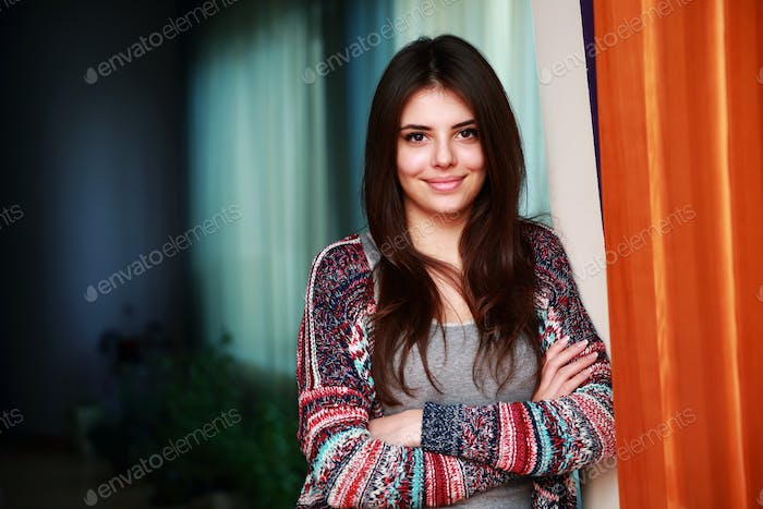 Portrait of a cute happy woman standing with arms folded at home