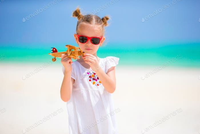 Happy little girl with toy airplane in hands on white sandy beach. Photo travel advertising, flights