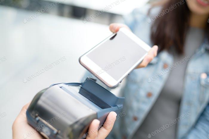 Frau, die mit NFC-Technologie auf dem Smartphone bezahlen