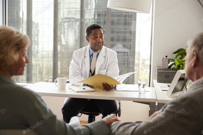 Senior Couple Having Consultation With Male Doctor In Hospital Office