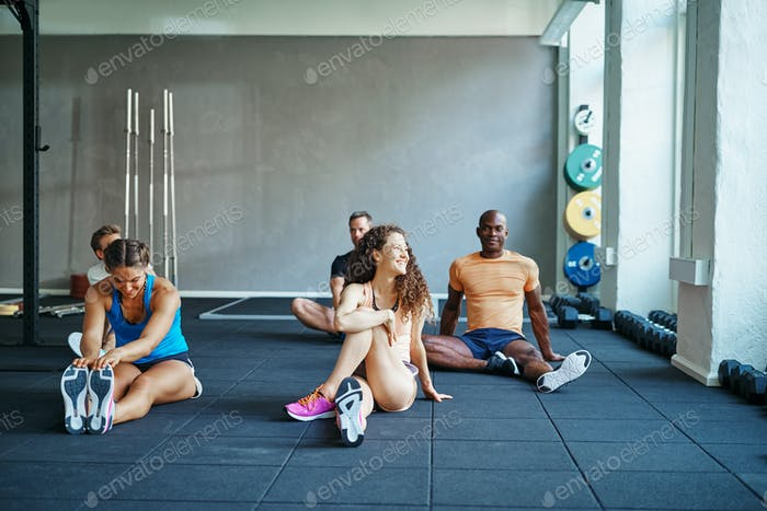 People laughing together on a gym floor after working out
