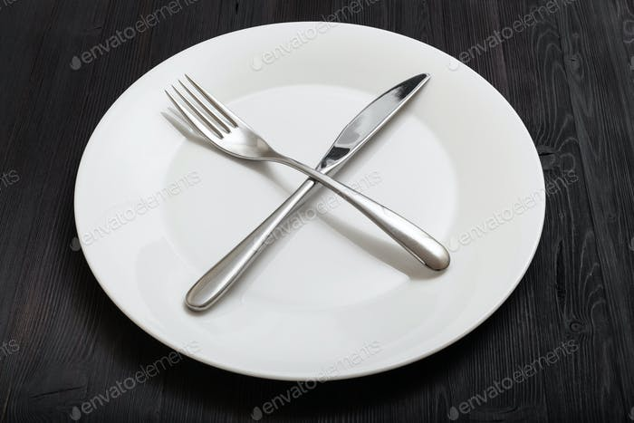 white plate with crossing knife, spoon on dark