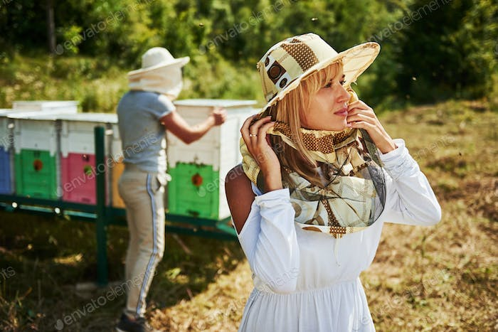 Portrait of two lovely beekeepers. Stands together near the hives