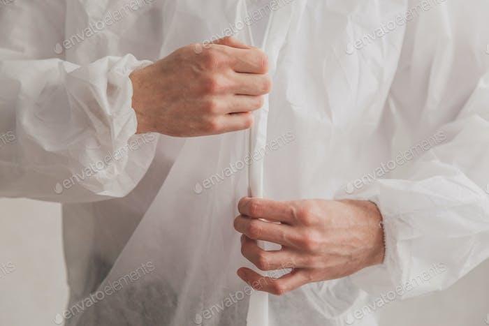 Doktor Epidemiologe zieht weiße Schutzhose an, schließt einen Reißverschluss, Hände schließen.