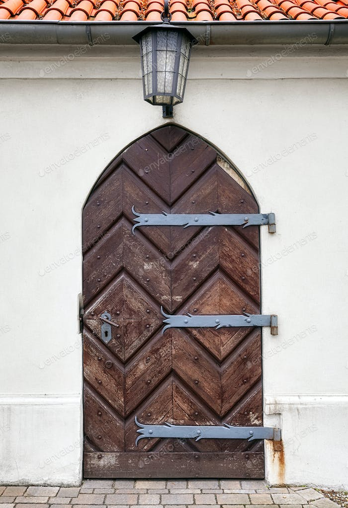 Old wooden door with a lamp above