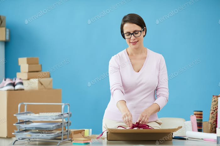Pretty female in pullover tying knot on top of parcel for client of online shop