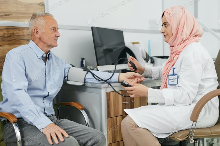 Middle-Eastern Female Doctor Talking to Senior Patient