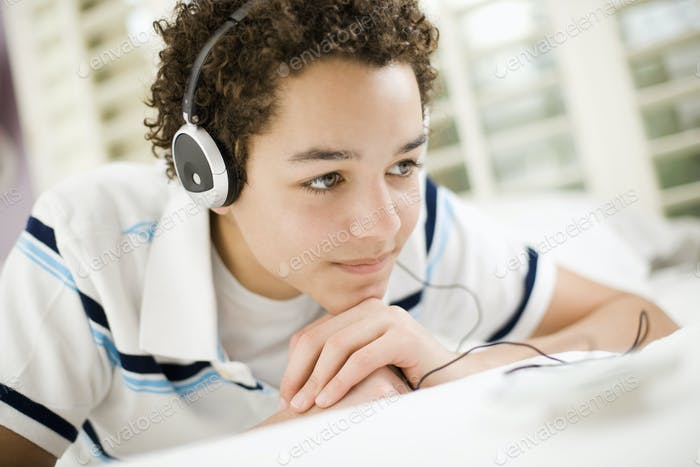 A boy wearing headphones lying on his stomach.