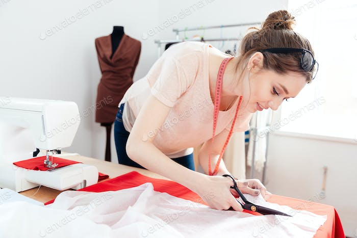 Focused woman fashion designer cutting white fabric in studio