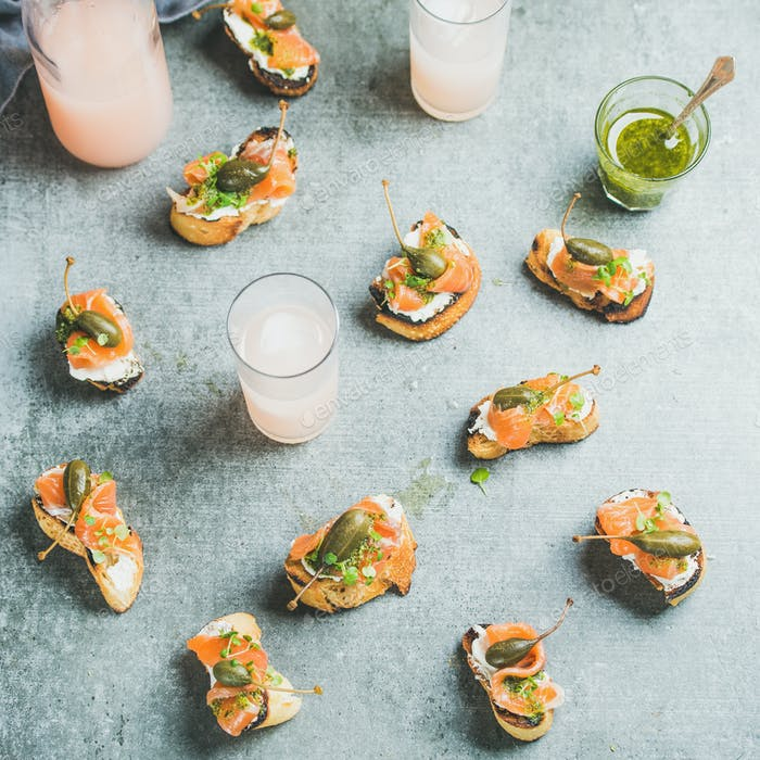 Crostini with smoked salmon, pesto sauce and grapefruit cocktails