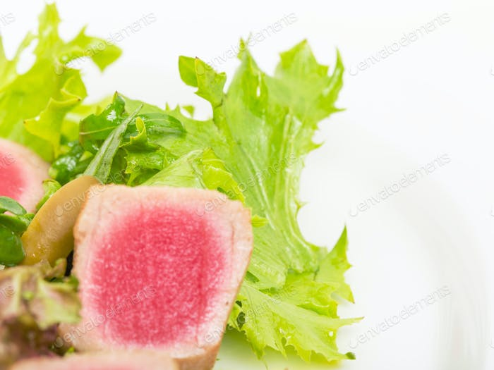 Grilled tuna fillet on fresh salad mix.