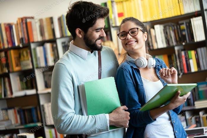 Glückliche Gruppe von Studenten, die in einer College-Bibliothek studieren und zusammenarbeiten