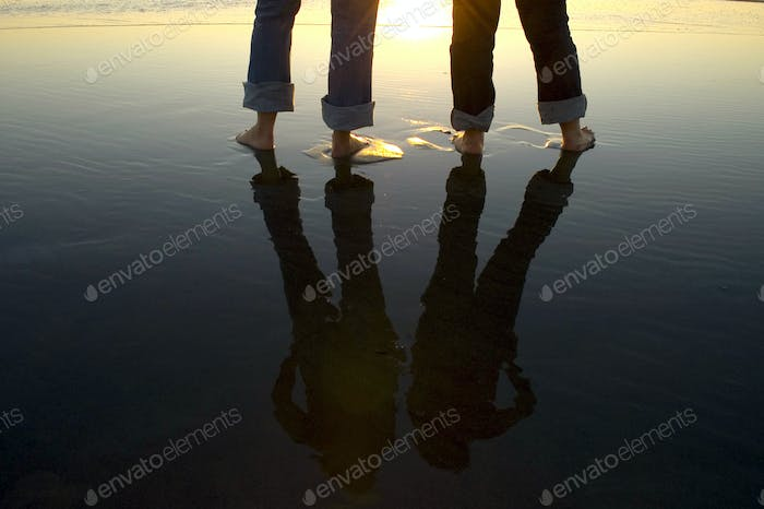 Reflection of legs in water at beach