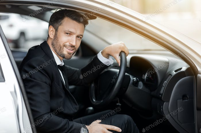 Happy young entrepreneur sitting in car, driving to airport