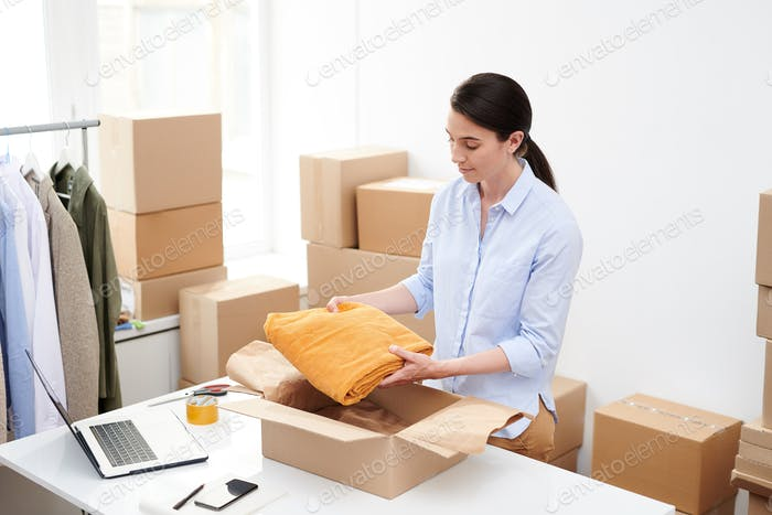 Young female online shop manager putting folded velvet yellow trousers into box
