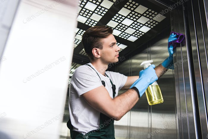 low angle view of handsome young cleaner washing elevator with rag and detergent