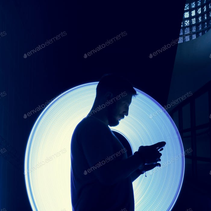 Closeup of a man using mobile phone in the dark with long exposure light