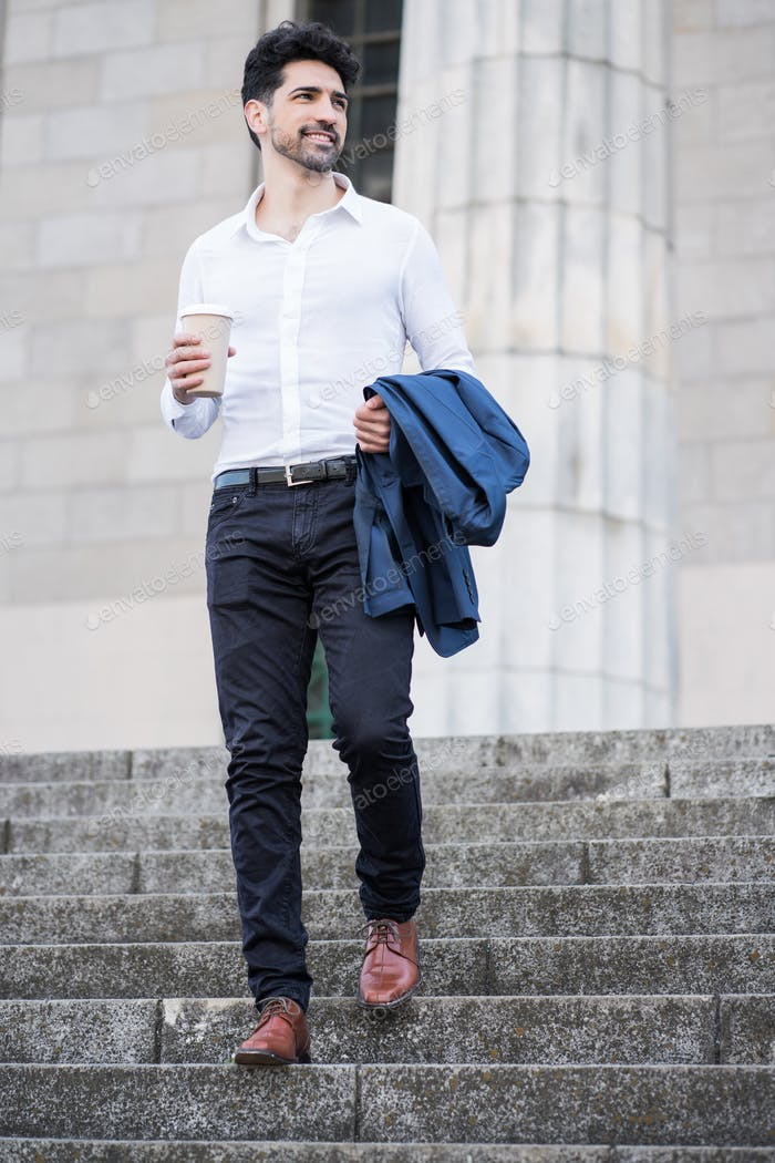 Businessman holding a cup of coffee on way to work.