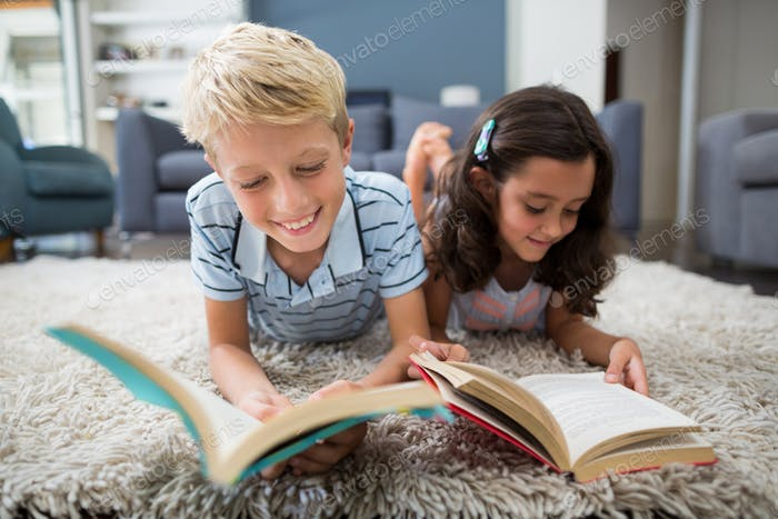 Siblings lying on rug and reading book in living room