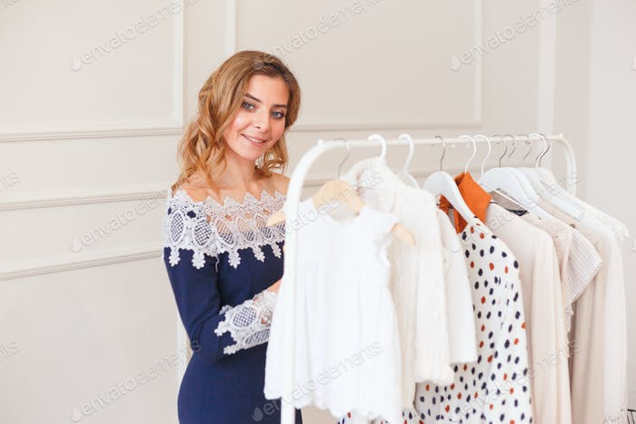 Young woman choosing clothes on a rack for the party