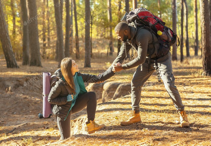 Gentlle man helping woman while hiking in mountain forest