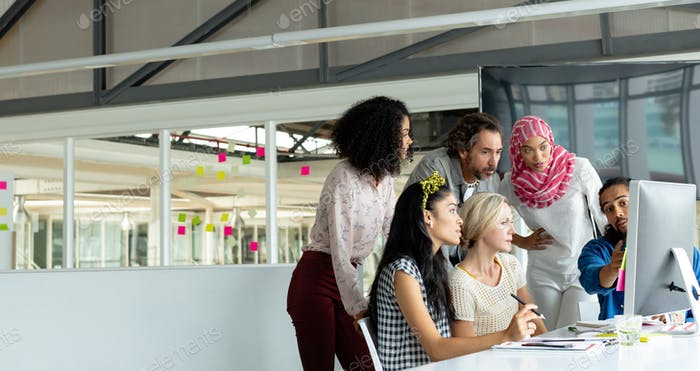 Diverse business people working together on computer