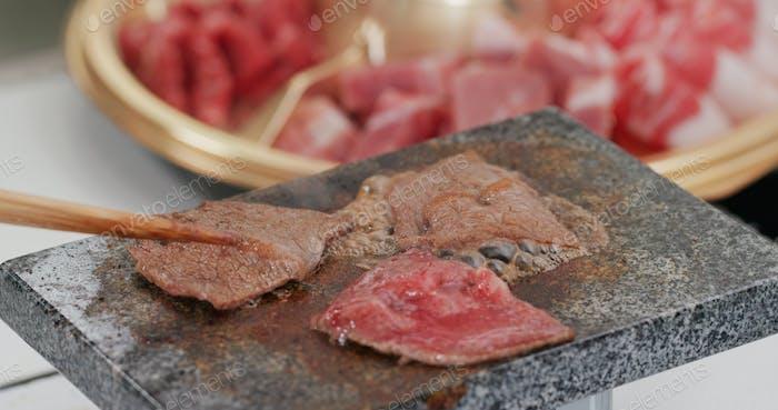 Grillen Sie Rindfleisch und Fleisch auf dem Steinstein