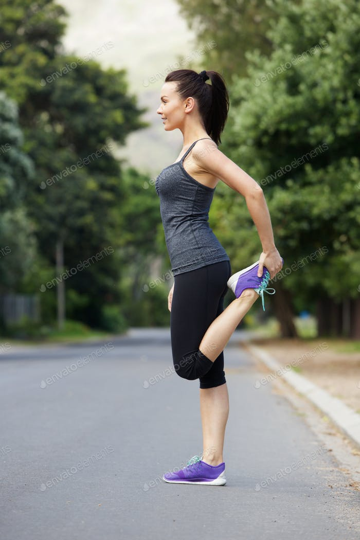 Sporty young woman doing stretching exercise outdoors
