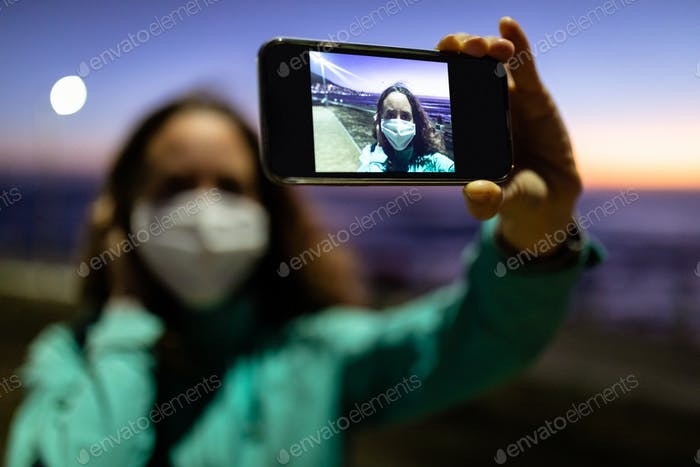 Caucasian woman wearing a protective mask against coronavirus, taking a picture in the streets