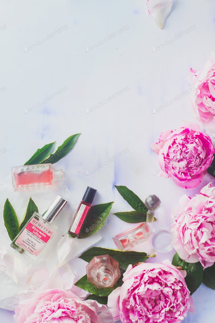Minimal styled flat lay with peony flowers with petalsand perfume bottles on a pastel background