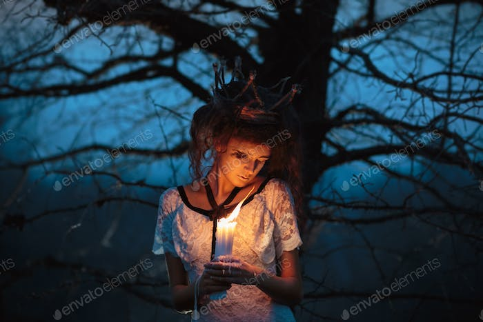 Young girl in the image of a bride with lighted candles in their