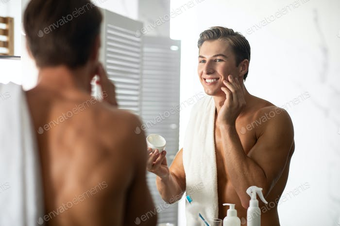 Handsome guy looking in the mirror applying cream