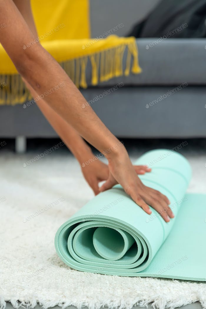 Anonymous woman unrolling her yoga mat at home