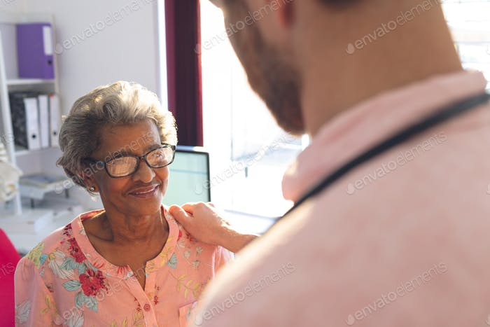 Rear view of a Caucasian confident male doctor interacting with female senior patient in clinic